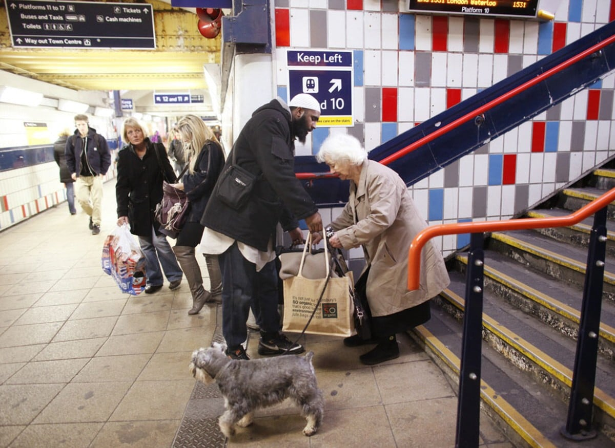 Hussain, a 34 year old Muslim, helps an elderly lady with her bags at the train station in London.