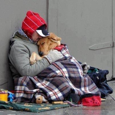 A homeless man and his dog keep each other warm.