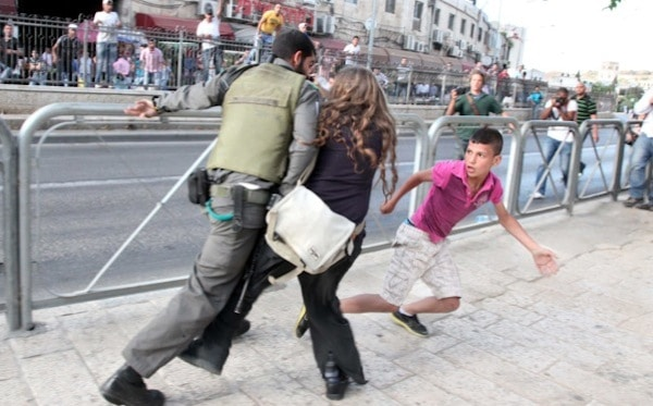 Israeli woman protects Palestinian boy from soldier...